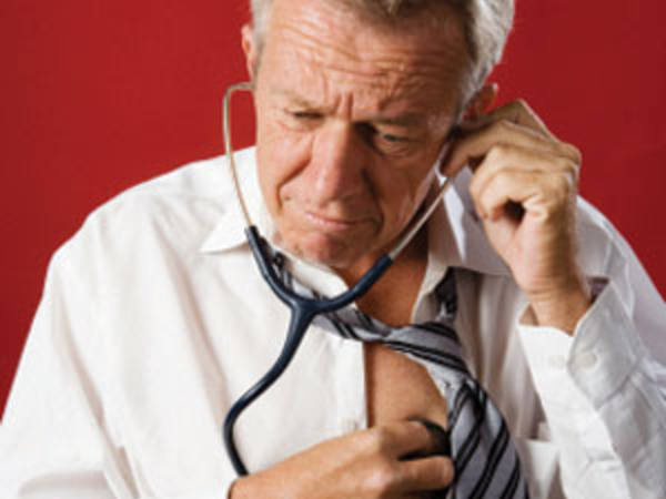 Photo: Man with a Stethescope Checking his Own Vitals