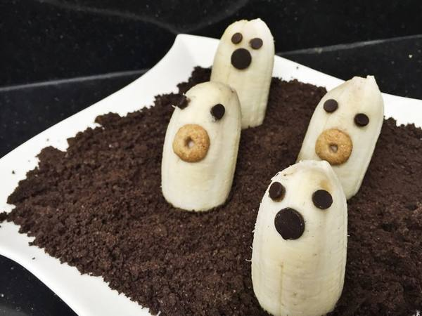 Photo: Half Bananas with chocolate chips and cereal made to look like ghosts