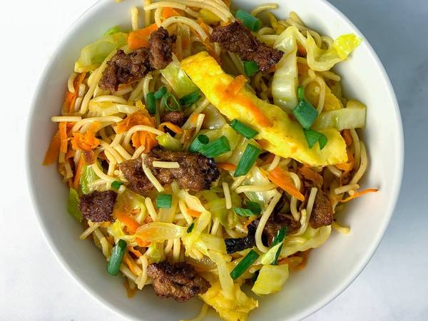 Bowl of fried noodles, vegetables and vegan char siu meat