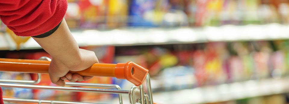 Photo: Lady pushing a shopping cart in the supermarket