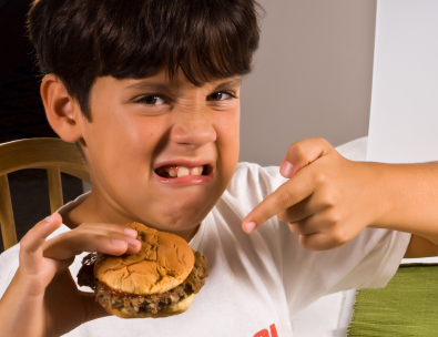 Photo: Boy Frowning and Holding a Burger