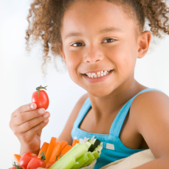 Photo: Girl Smiling and Holding a Tomato