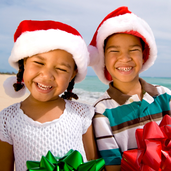 Photo: Boy and Girl holding Christmas Gifts on the Beach