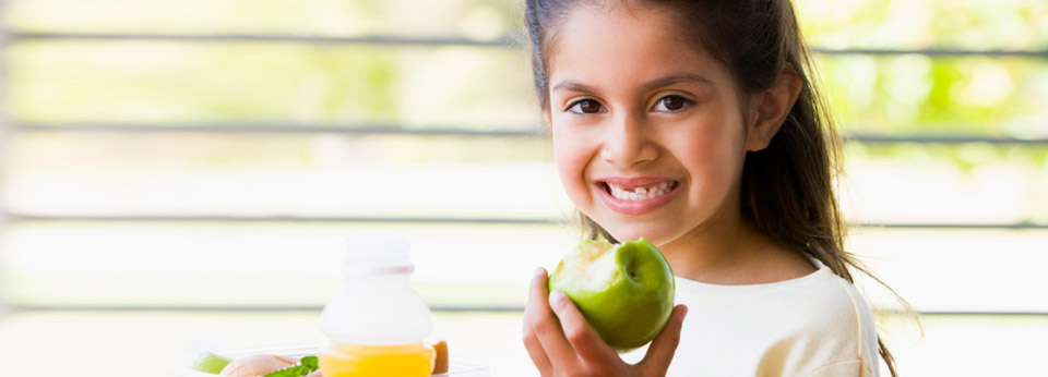 Photo: Girl Smiling and Eating an Apple