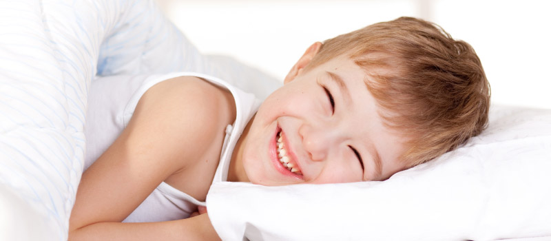 Photo: Boy Smiling in Bed