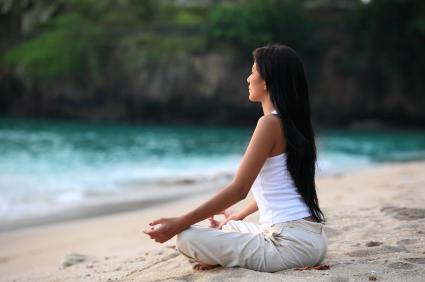 Photo: Woman Meditating on the Beach