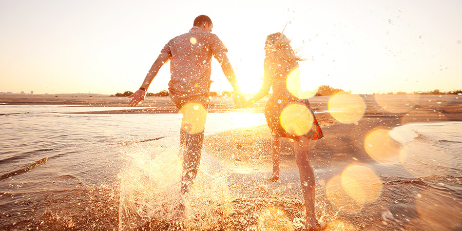 Photo: Couple Holding Hands and Running on the Beach