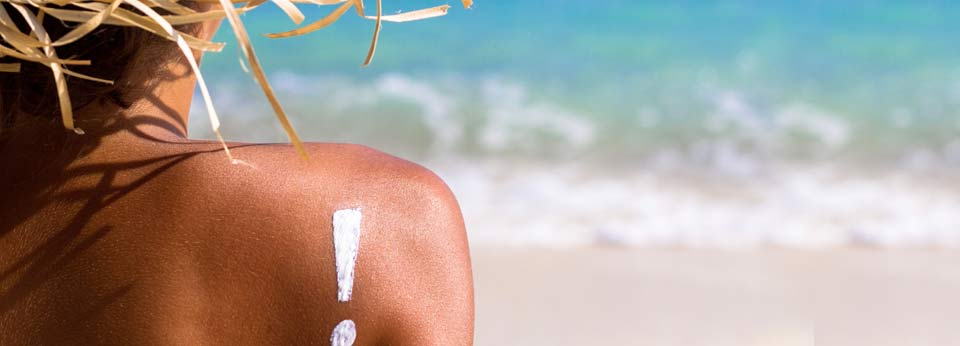 Photo: Person on a Beach with Sunscreen in the Shape of an Exclamation Point