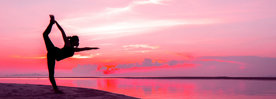 Photo: Woman Doing Yoga on the Beach