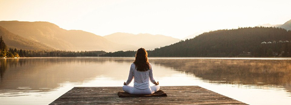 Photo: Woman meditating by a lake